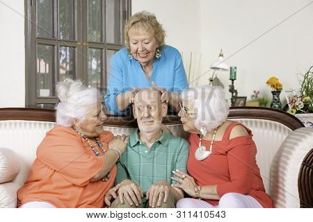 Three Senior Women Giving Affection To A Nervous Man
