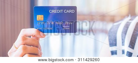 Woman Hand Holds A Blue Credit Card.