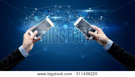 Close up of two hands holding smartphones and sharing business data