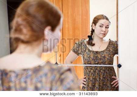 Portrait Of Young Caucasian Female In Dress Standing Against Mirror And Looking At Herself In Domest