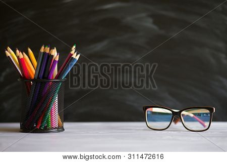 Glasses Teacher And Stand With Pencils On Table, On Background Of Blackboard With Chalk. Concept Of