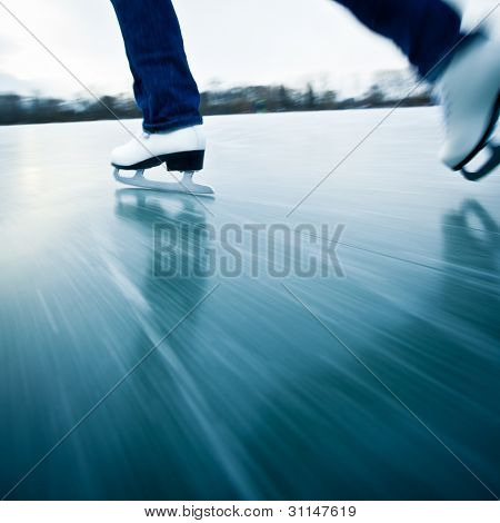 Young woman ice skating outdoors on a pond on a freezing winter day - detail of the legs (motion blur is used to convey speed; color toned image)