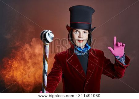 Fabulous Circus Man In A Hat And A Red Suit Posing In The Smoke On A Colored Dark Background. A Clow
