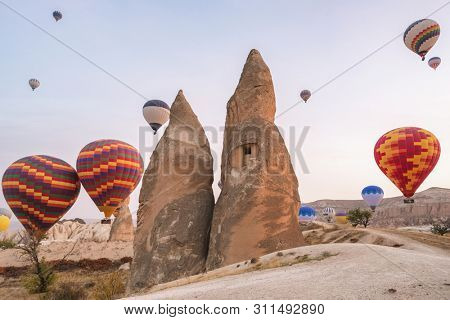 Hot air balloons flying over famous rock formations landscape of Cappadocia, Turkey