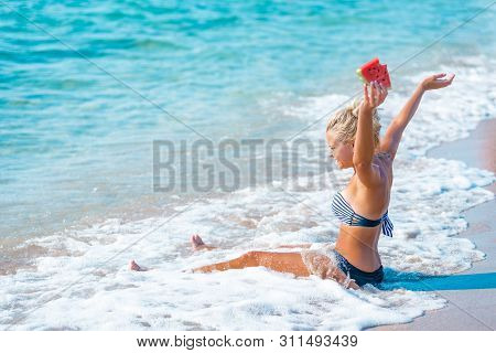 Happy Woman Relaxing On The Beach On A Summer Day Smiling With A Slice Of Watermelon In Her Hand