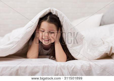 Happy Morning Baby In Bed. Child Dabbles In Bed. Child Covers His Ears