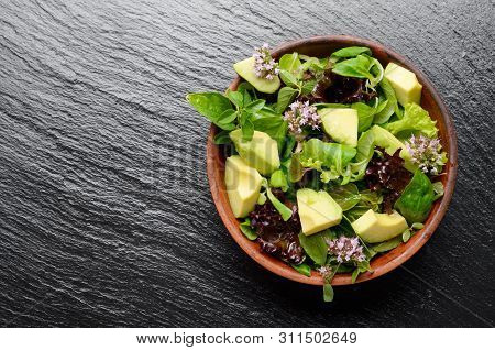 Top View At Clay Dish With Salad Of Avocado, Green And Violet Lettuce, Lamb's Lettuce And Oregano Fl