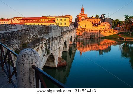 Rimini Cityscape At Sunset, Italy. Rimini Landmarks. Tiberius Bridge In Rimini In The Evening, Italy