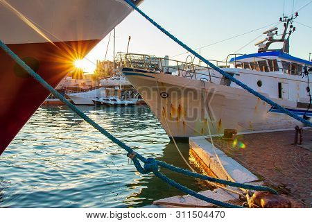 Fishing Ships In Sea Port At Sunset. Sun And Ship