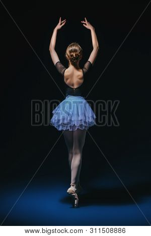 A full length portrait of an elegant refined ballet female dancer posing in the studio over the black background. Talent, fashion for ballet dancers.