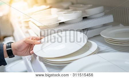 Male Hand Shopper Choosing With Ceramic Dish Or Plate In Grocery Store. Buying Tableware Or Kitchenw