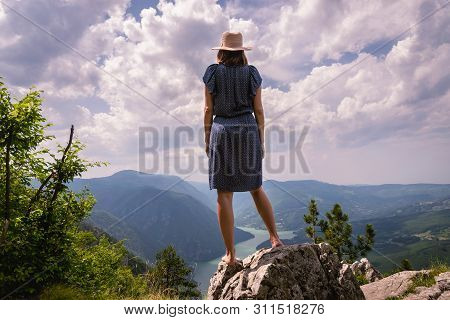 Traveler Girl On Mountain Cliff In Vacation. Young Girl Traveler In Vacation. Traveler Look To Mount