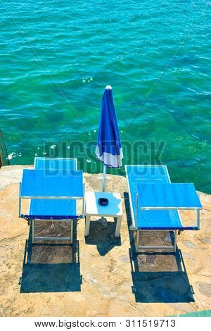 Beach chaise longues next to the sea at seaside resort