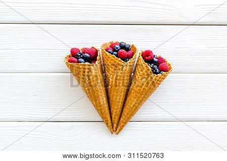 Summer Breakfast With Fresh Berries In Waffle Cones On White Wooden Background Top View