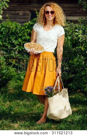 Young Middleaged Smiling Woman In Vibrant Summer Clothes Is Holding Full Wicker Grocery Shopping Bag