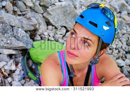 Woman Mountaineer With Helmet And Backpack, Sitting Down, Resting And Looking Up Towards A Rock Clim