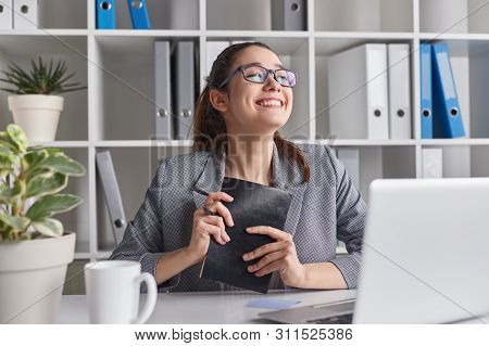Happy Young Lady With Notebook Smiling And Closing Eyes While Sitting At Desk In Office