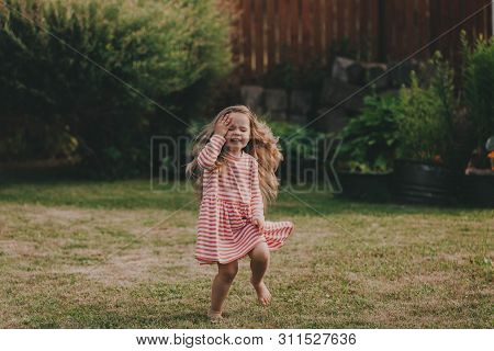Cute Baby Girl With Long Hair In A Striped Dress. Concept Of Holidays, Summer Fan, Insects Bite.
