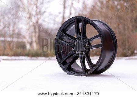 New Stylish Black Brushed Aluminum Alloy Wheel, On White Snow. Winter.