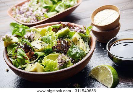 Clay Dish With Salad Of Avocado, Green And Violet Lettuce, Lamb's Lettuce And Oregano Flowers On Sla