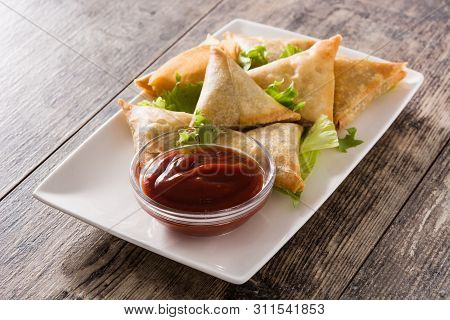 Samsa Or Samosas With Meat And Vegetables On Wooden Table. Traditional Indian Food.