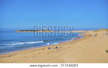 Barbate, Spain - June 25, 2019. Panoramic view of the Cove of Varadero, Marisucia beach with The Trafalgar Lighthouse in the background. Los Canos de Meca, Barbate, Cadiz, Andalusia, Spain.