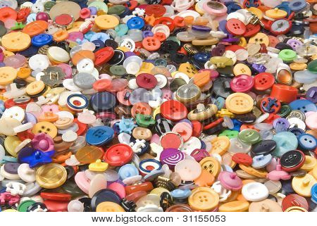 Collection of many different colourful buttons spread out.