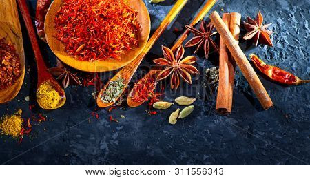 Spices. Various Indian Spices on black stone table. Spice and herbs on slate background. Assortment of Seasonings, condiments. Cooking ingredients, flavor. Cardamom, safran,