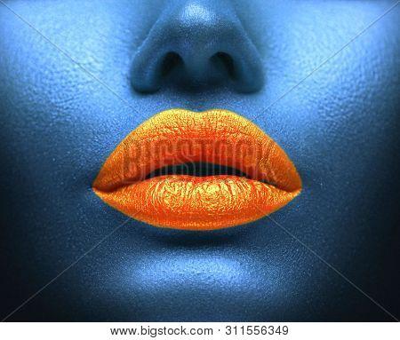 Creative colorful Make-up, Orange lips on glue skin Art design. Paint the face, lip, bodyart, lipgloss on sexy lips, beautiful model girl's mouth, blue color skin make-up. Beauty woman makeup close up