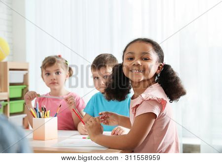Cute Children Drawing Together At Table Indoors. Kindergarten Playtime Activities