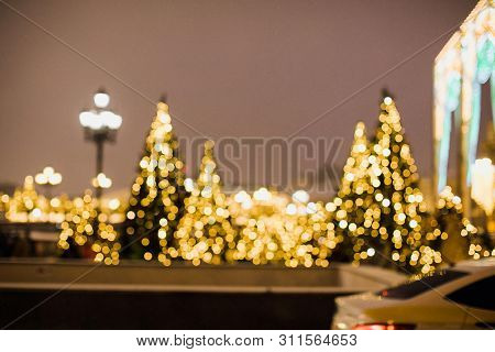 Christmas Background With Unfocused Christmas Tree By Night. City Decorated With Christmas Lights