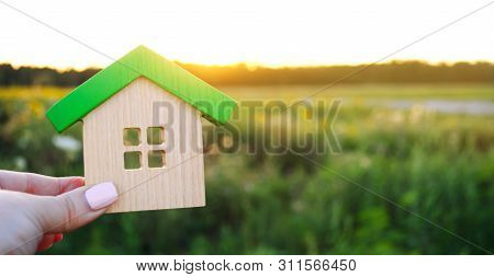 Wooden House In The Hands In The Sunset Background. Real Estate Concept. Eco Friendly Home. Symbol O