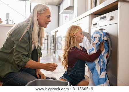 Smiling senior woman with cute girl loading washing machine at home. Grandmother and granddaughter putting dirty clothes into washing machine. Little happy grandchild sitting on floor helping granny.