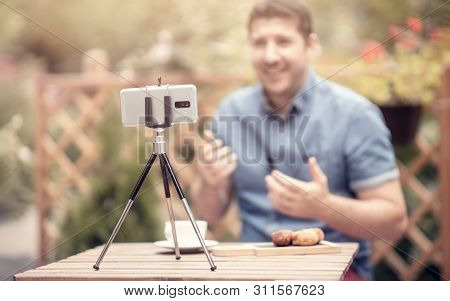 Blogger Speaking And Gesturing In Front Of Camera. Selective Focus On Smart Phone Mounted On A Tripo