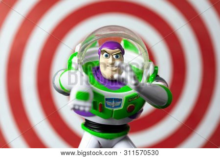 JULY 7 2019: Buzz Lightyear in an action pose from the Toy Story movie franchise with red ring background illustrating his laser beam feature - Disney action figure - Image