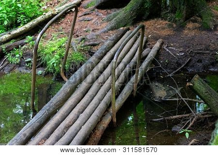 Old Bridge Of Logs Over The River In The Forest