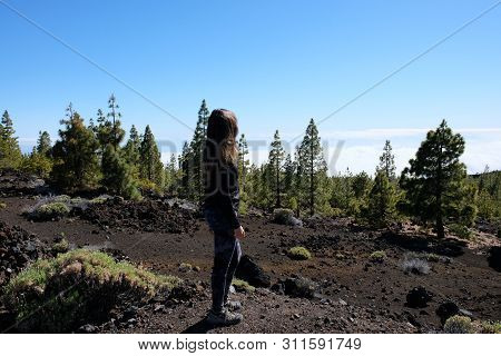 Woman Ascending The Teide Mountain Peak On A Dry And Rocky Volcanic Landscape