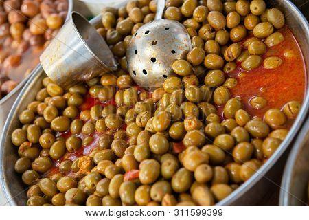 Selective large pickled olives in brine in outdoor market