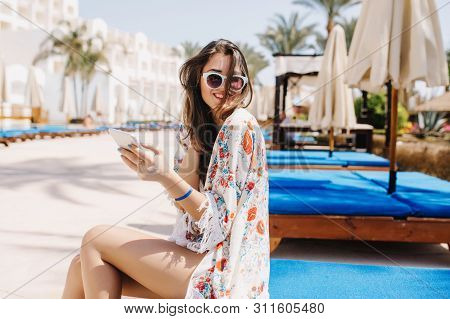 Amazing Tanned Girl With Dark Hair Laughing, Sitting On Blue Trestle-bed Near The Pool. Gorgeous Bru