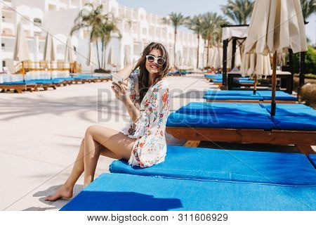 Joyful Barefooted Lovely Girl Resting On Blue Chaise-longue And Smiling To Camera With Palm Trees On