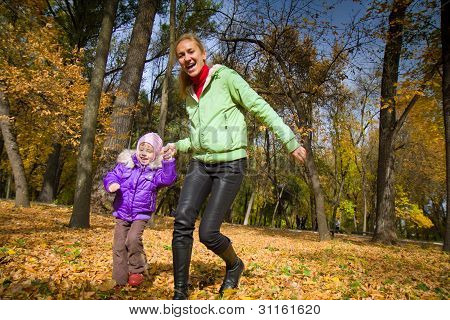 Woman Flees With Her Daughter In The Autumn Park
