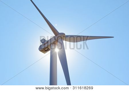 Wind Generator Turbine in Bright Sun Light on the Clear Blue Sky Bacground. Green Renewable Energy Concept.