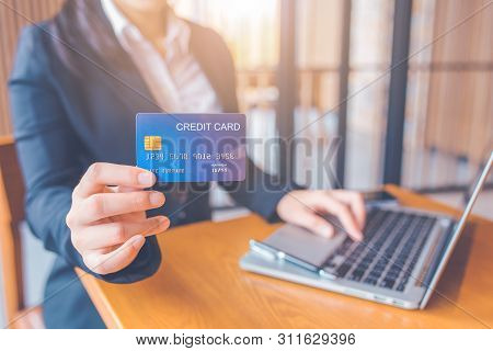 Business Woman Hand Holds A Blue Credit Card.and Are Using A Laptop Computer