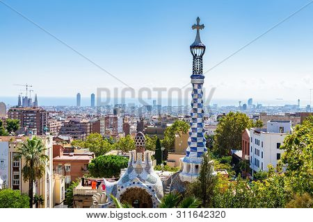 Aerial View On Barcelona City With Iconic Tower Of Park Guell