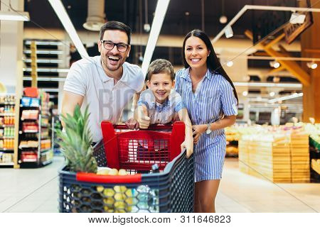 Happy Family With Child And Shopping Cart Buying Food At Grocery Store Or Supermarket