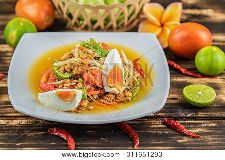 Somtum. Thai Spicy Green Papaya Salad With Salted Egg On Wooden Table.(somtum Khai Kem)