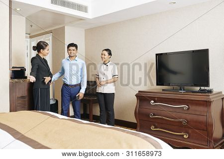 Asian Manager Of The Hotel Together With Maid Meeting The Businessman As Guest Of The Hotel And Show