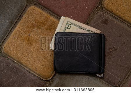 Old Lost Wallet With A Few Dollar Bills Wallowing On The Sidewalk