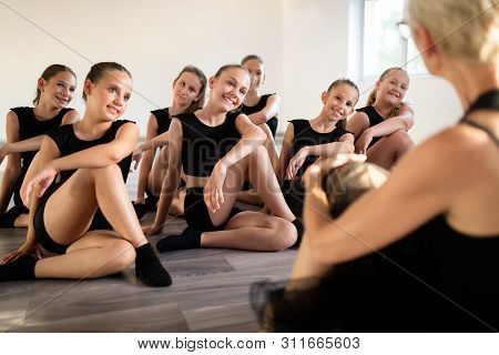 Teacher And Group Of Children Exercising Dancing And Ballet In Dance School