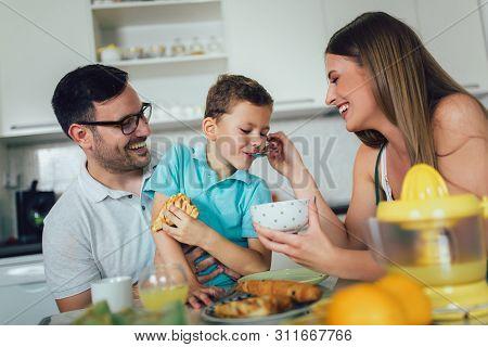 Family Eating Breakfast At Kitchen Table, Having Fun